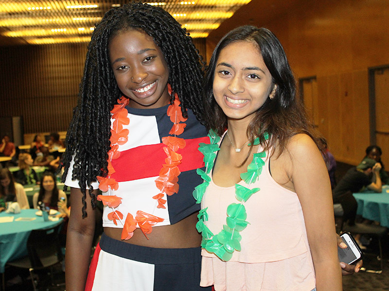 Two girls smile at the camera at an event.